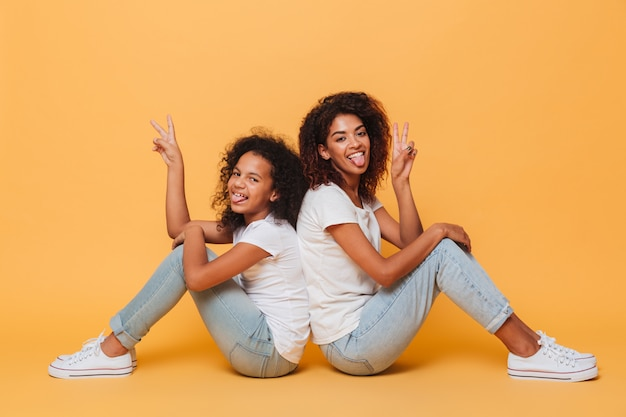Full length of two african sisters sitting back to back Free Photo