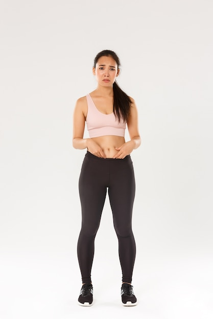 Full length of upset and gloomy asian girl in fitness clothing, showing fat on belly, complaining on body, frowning and looking disappointed, starting workout, trying lose weight, white background. Free Photo