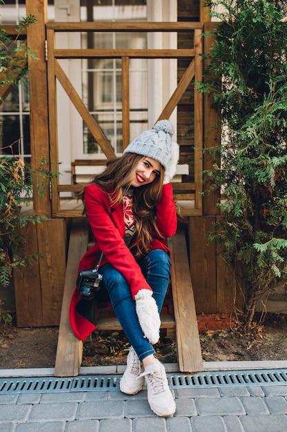 赤いコートと屋外の木製の階段の上に座ってニット帽子の長い髪の完全な長さの垂直ブルネットの少女。彼女は暖かい白い手袋を着用し、笑っています。 無料写真