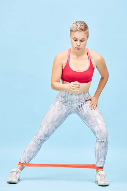 Full length vertical shot of self determined athletic girl doing cardio workout performing standing lateral steps or walks using resistance band to train glutes, hamstrings, calves and quadriceps Free Photo