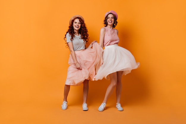 Full length view of enthusiastic girls with curly hair dancing with smile. studio shot of glad female friends having fun on yellow background. Free Photo