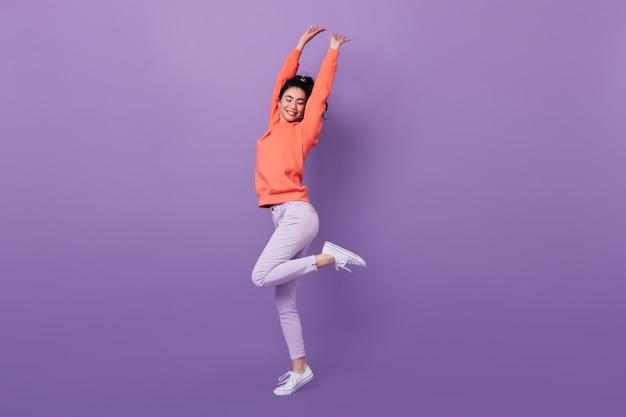 미소로 춤을 화려한 아시아 여자의 전체 길이보기. 한쪽 다리에 서있는 매력적인 한국 모델의 스튜디오 샷. 무료 사진