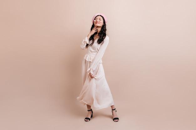 Вид в полный рост корейской девушки в берете. стильная азиатская модель позирует на бежевом фоне. Бесплатные Фотографии