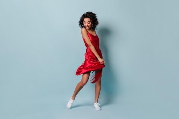 Вид в полный рост игривой молодой женщины, танцующей на синей стене Бесплатные Фотографии