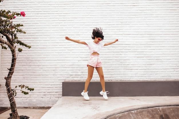 通りをジャンプして喜んでいる女性の完全な長さのビュー。ショートパンツで魅力的な日焼けした女性の屋外ショット。 無料写真