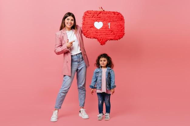 Вид в полный рост модных мамы и дочери, позирующих с как значок. студия выстрел из семьи с символом социальной сети. Бесплатные Фотографии
