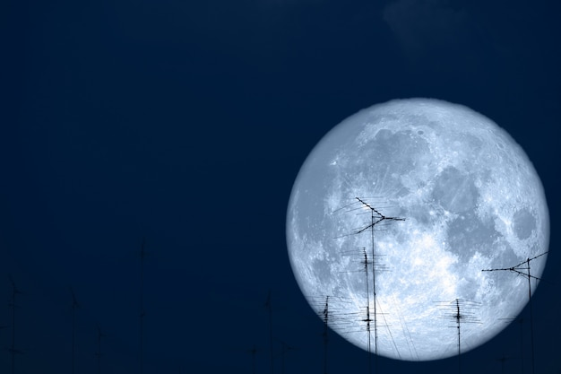 Full milk moon back on silhouette antennas on the night sky Premium Photo