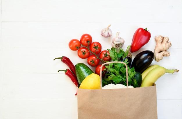 Полный бумажный пакет здоровой пищи на белом фоне. эко-шоппинг и концепция доставки еды. концепция нулевых отходов. Premium Фотографии