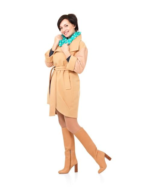 Ritratto completo della donna felice nello stivale di cuoio del cappotto di caduta con la condizione verde della sciarpa isolata su bianco Foto Gratuite
