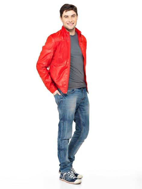 Полный портрет улыбающегося счастливого красивого человека в красной куртке, синих джинсах и тренажерных залах. красивый парень, стоящий на белом фоне Бесплатные Фотографии