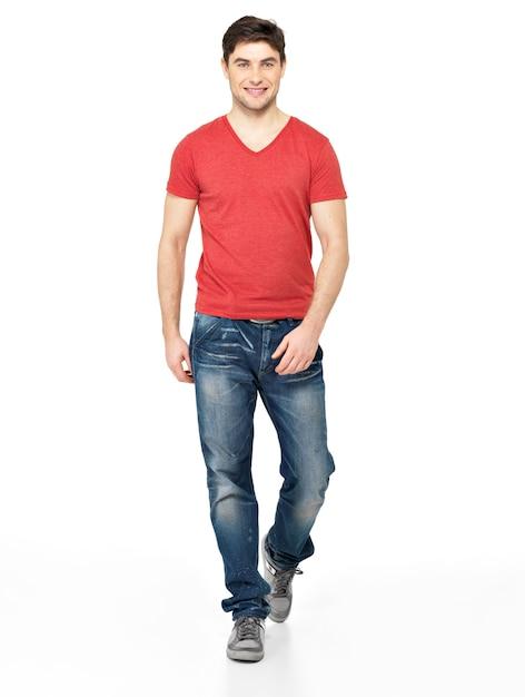Полный портрет улыбающегося идущего человека в красной футболке вскользь, изолированных на белом фоне. Бесплатные Фотографии
