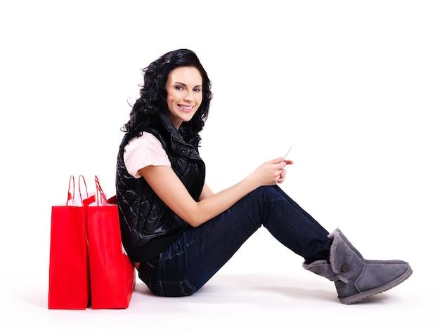 床に座っている赤い買い物袋と笑顔の女性の完全な肖像画-白で隔離。 無料写真