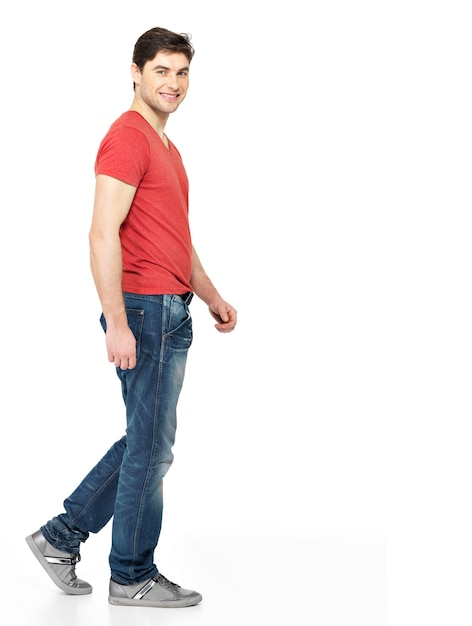 Full portrait of smiling  walking man in red t-shirt casuals  isolated on white background. Free Photo