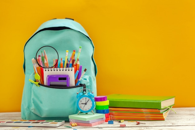 Full school backpack with different supplies on orange background. Premium Photo