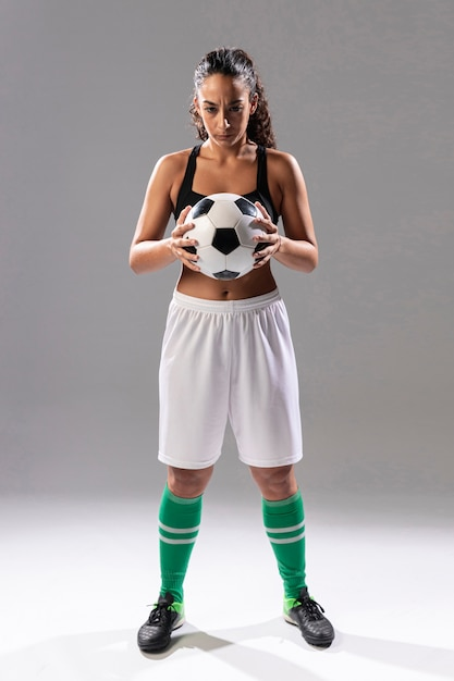 Full shot adult woman holding soccer ball Free Photo