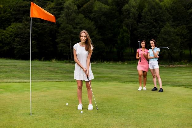 Full shot beautiful girl playing golf Free Photo