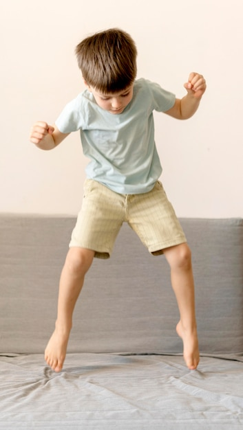 Full shot boy jumping on couch Free Photo