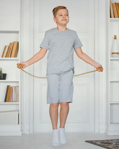 中の縄跳びの少年のフルショット 無料写真