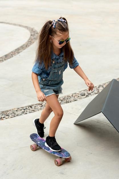 Full shot of child on skateboard Free Photo