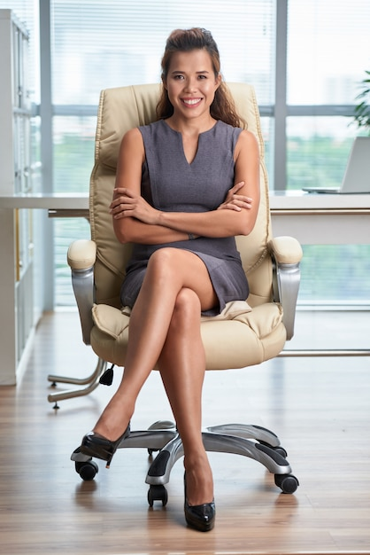 Full shot of confident lady sitting leg over leg in the office chair with arms folded Free Photo
