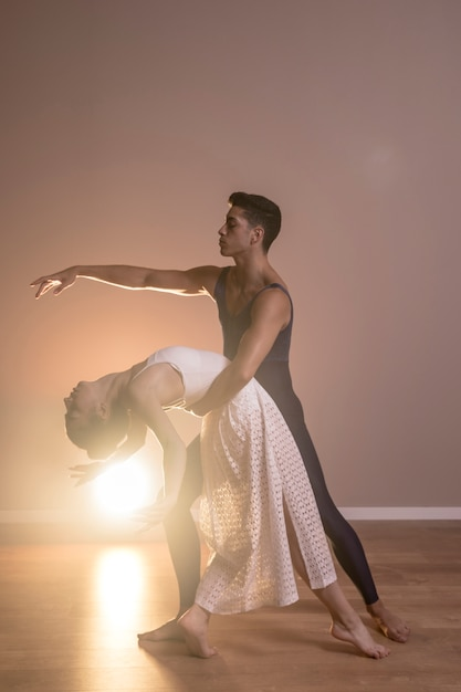 Full shot couple dancing together Free Photo