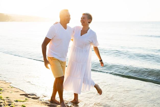 Полный снимок пара, развлекающаяся на берегу моря Бесплатные Фотографии