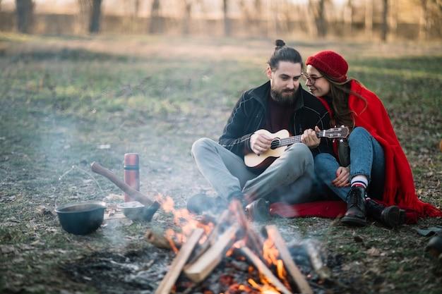 キャンプファイヤーの近くのフルショットのカップル 無料写真