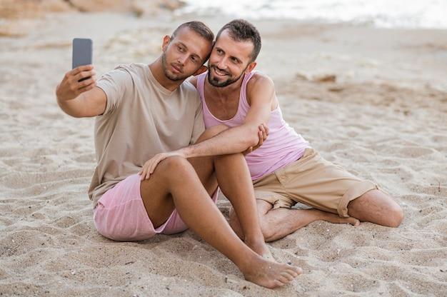 ビーチで自分撮りを撮るフルショットカップル 無料写真