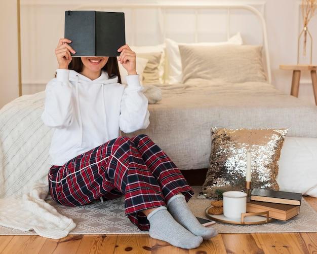本と軽食と敷物の上に座っているフルショットの居心地の良い女性 Premium写真
