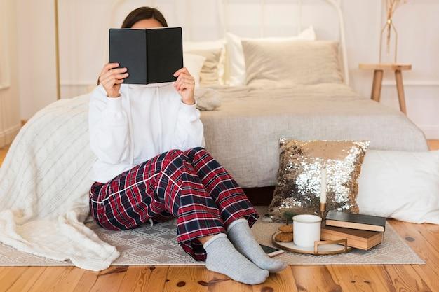 本と敷物の上に座っているフルショットの居心地の良い女性 Premium写真