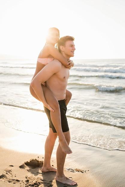 ビーチでフルショットのかわいいカップル 無料写真