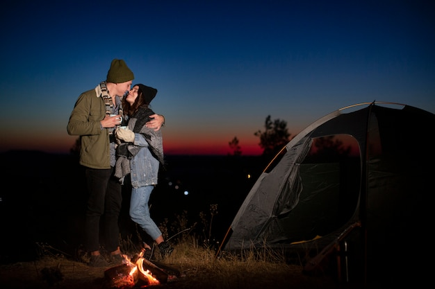 Full shot cute couple kissing in the nature Free Photo