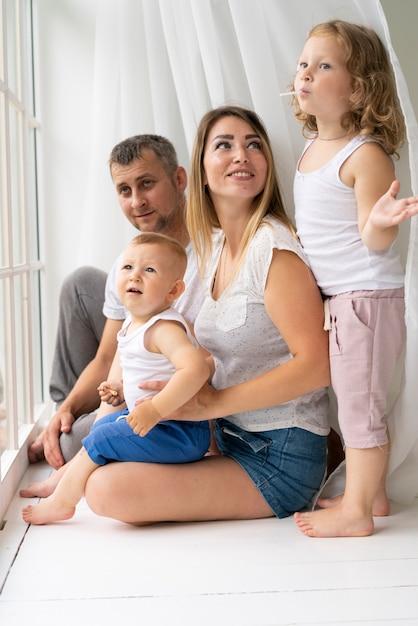 フルショットの家族が一緒に窓の近くにいる 無料写真
