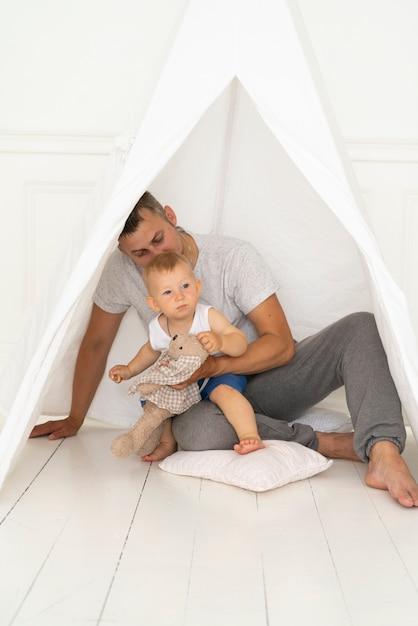 テントの下で男の子と一緒に座っているフルショットの父 無料写真