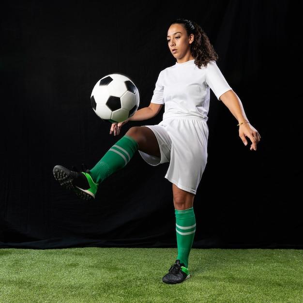 Full shot female playing football Free Photo