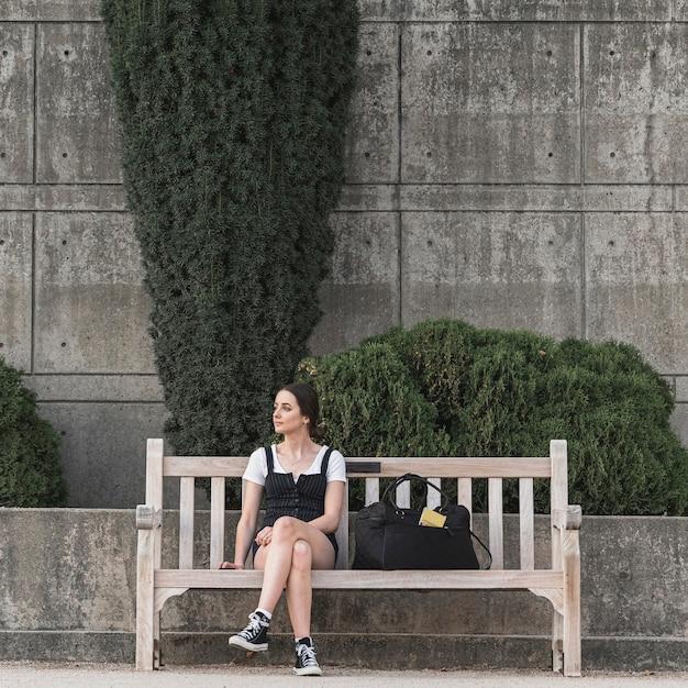 Полный выстрел женщина сидит на скамейке Бесплатные Фотографии