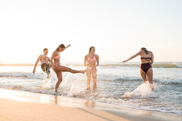 Full shot friends having fun at beach Free Photo