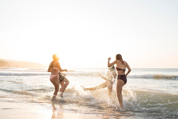 Full shot friends having fun on shore Free Photo