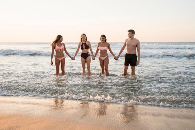 Полный снимок друзей, взявшись за руки на пляже Бесплатные Фотографии