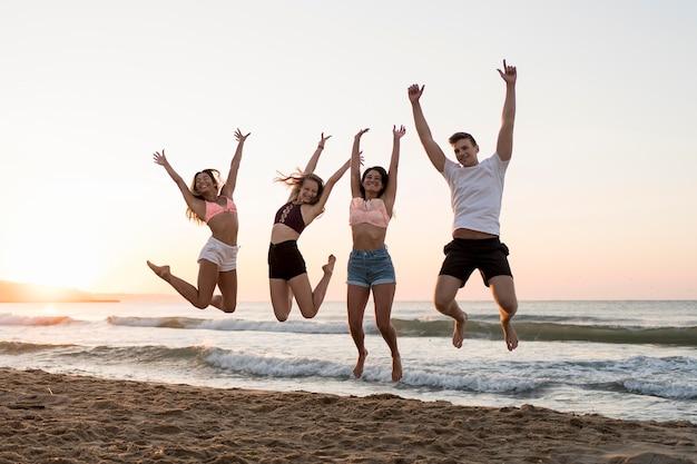 ビーチでジャンプフルショットの友人 無料写真