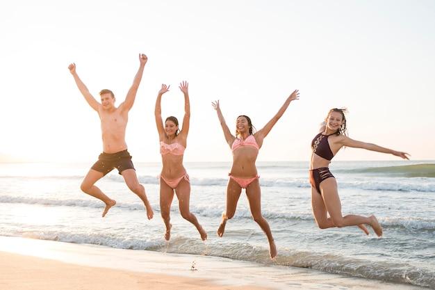 海岸でジャンプフルショットの友達 無料写真