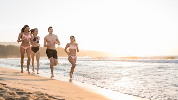 Full shot friends running together on shore Free Photo