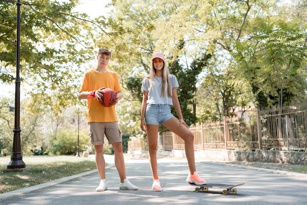 Amici del colpo pieno con skateboard e palla Foto Gratuite