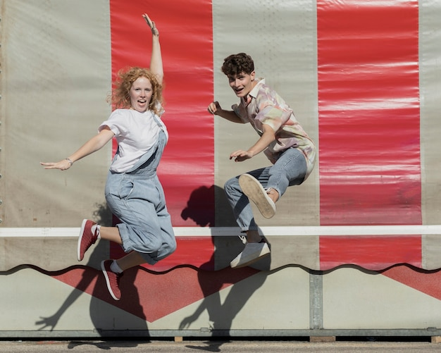 Full shot funny couple jumping together Free Photo