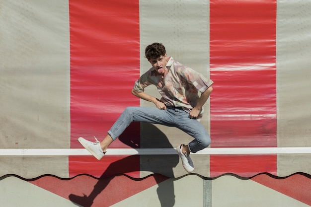 Full shot funny guy jumping outdoors Free Photo