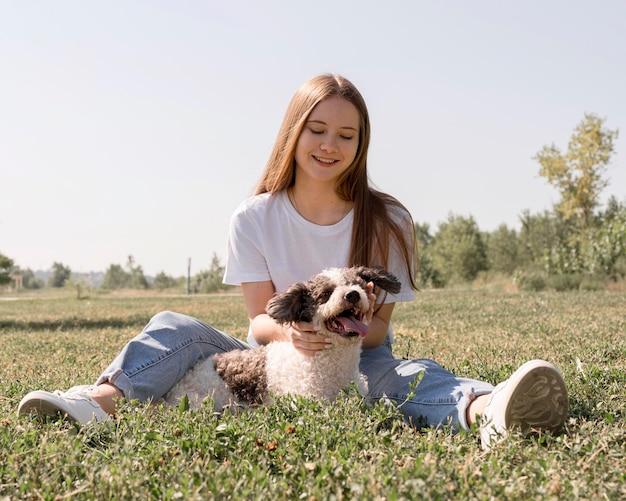 Полный выстрел девушка сидит на траве с собакой Бесплатные Фотографии