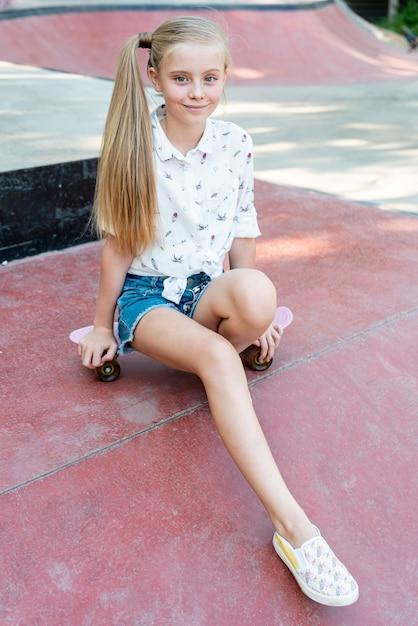 Full shot of girl sitting on skateboard Free Photo
