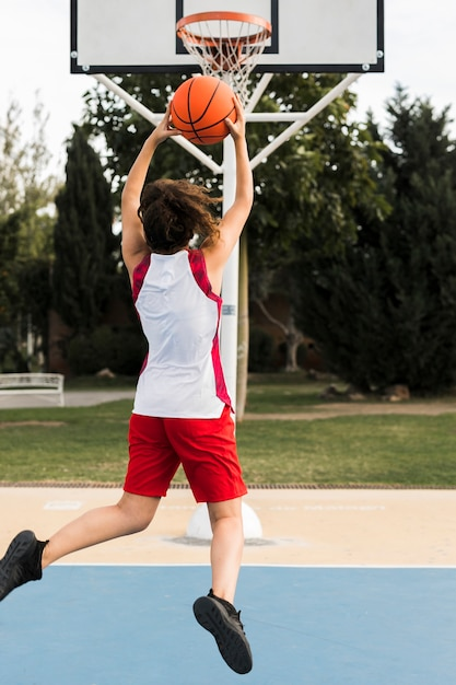 Full shot of girl throwing in the basketball hoop Free Photo