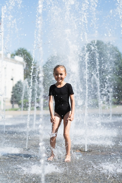 Full shot of girl at water fountain Free Photo