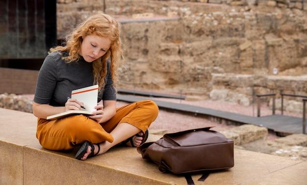 ジャーナルに書いているフルショットの女の子 無料写真
